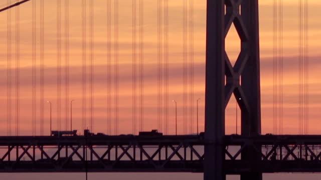 silhouette cars on double decker bridge during sunrise - san francisco bay bridge stock videos and b-roll footage