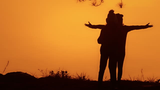 Silhouette couple woman looking at amazing sunset together