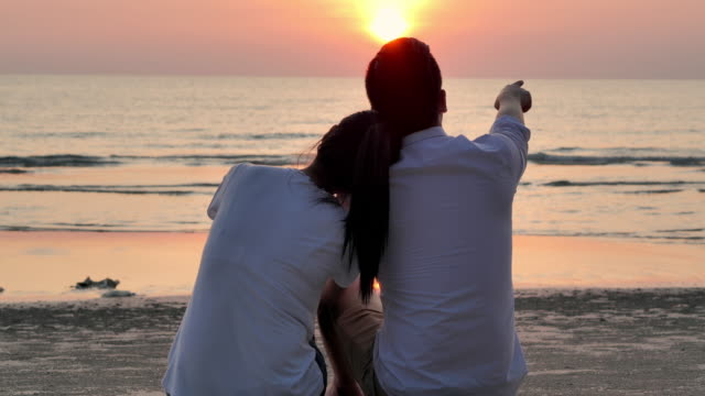 silhouette couples sitting with fun along edge of sunset sea surf on sand beach.happy family holidays.family,lifestyle,people,life insurance,vacations,non-caucasian honeymoon - husband stock videos & royalty-free footage