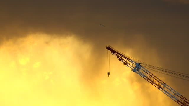 silhouette crane in building construction site on sunset background - construction machinery stock videos & royalty-free footage