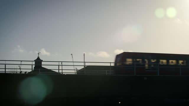 silhouette dlr train over bridge at sunrise - passenger train stock videos & royalty-free footage