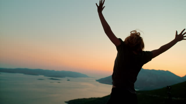 ms silhouette exuberant woman jumping for joy at scenic overlook at dusk,peljesac,croatia - arms raised stock videos & royalty-free footage