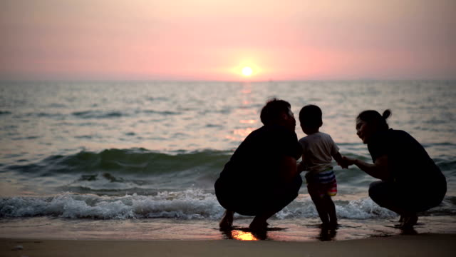 silhouette family and baby boy holding hands walking together on the beach at sunset. - family with two children stock videos & royalty-free footage