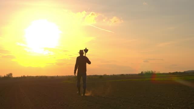 ms-silhouette bauer mit hacke in idyllischer, ländlicher gepflügtes feld bei sonnenuntergang - jäthacke stock-videos und b-roll-filmmaterial