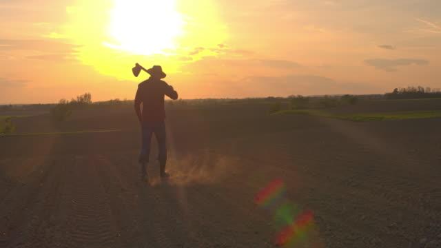 ms silhouette jordbrukare transporterar hoe i idylliska, lantliga upplöjd fältet vid solnedgången - gröda bildbanksvideor och videomaterial från bakom kulisserna
