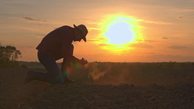 MS-Silhouette Landwirt in idyllischer, ländlicher Gepflügtes Feld bei Sonnenuntergang
