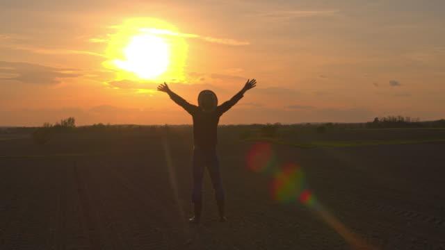 MS-Silhouette Bauer Stand auf sonnigen, idyllischen ländlichen Gebiet bei Sonnenuntergang