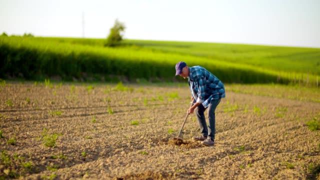 Silhouette farmer using hoe in rural plowed field