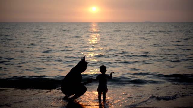 vídeos y material grabado en eventos de stock de silueta de padre e hijo cogidos de la mano caminando por la playa al atardecer. - padre con hijo