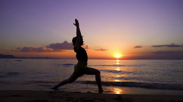 silhouette femmina con posa surya namaskar yoga sulla spiaggia - zen video stock e b–roll
