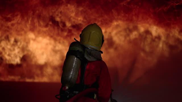 消火器を使用した消火オレンジのスーツのシルエット消防士。 - 救助隊点の映像素材/bロール