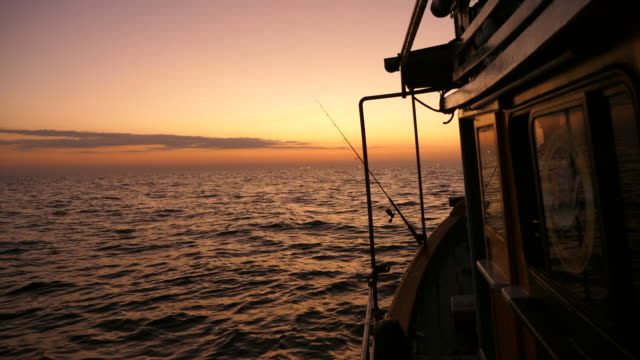 silhouette fishing boats with golden sunset in a sea - trawler stock videos & royalty-free footage