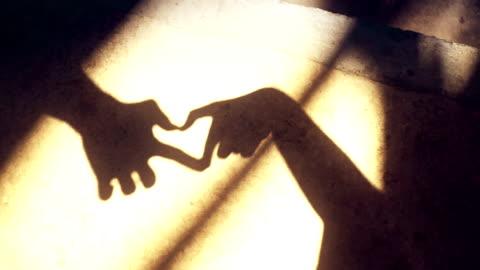 vídeos y material grabado en eventos de stock de silueta que forma la sombra de forma de corazón por manos en el suelo para el día de san valentín. - sombra