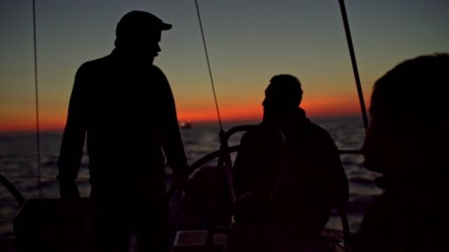 4k silhouette freunde auf segelboot am sonnenuntergang ozean, real-time - besatzung stock-videos und b-roll-filmmaterial