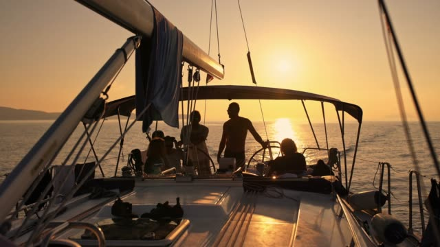 4k silhouette friends on sailboat on sunny, tranquil sunset ocean, real time - yacht stock videos & royalty-free footage