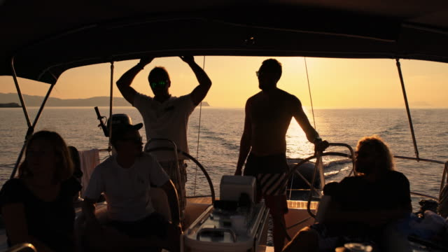 4K Silhouette friends on sailboat on sunny, tranquil sunset ocean, real time