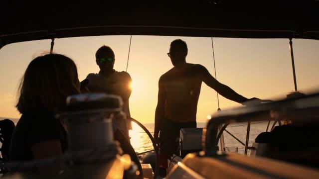 vídeos de stock, filmes e b-roll de amigos de silhueta 4k em veleiro no oceano do sol ensolarado e tranquilo, em tempo real - tripulação