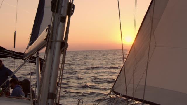 vídeos de stock e filmes b-roll de 4k silhouette friends on sailboat on tranquil sunset ocean, slow motion - veleiro
