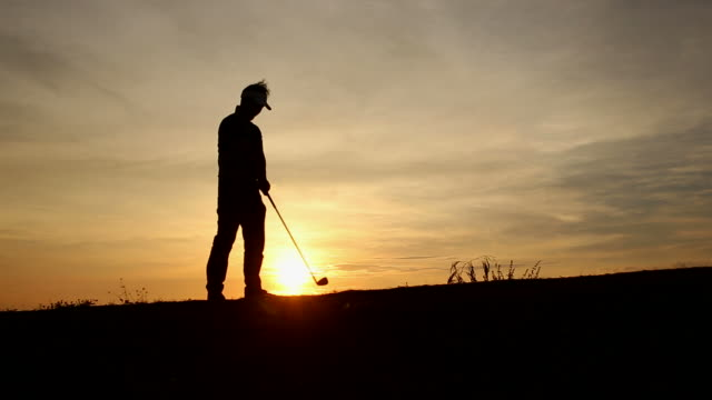 silhouette golfer at sunset - golf swing motion stock videos & royalty-free footage