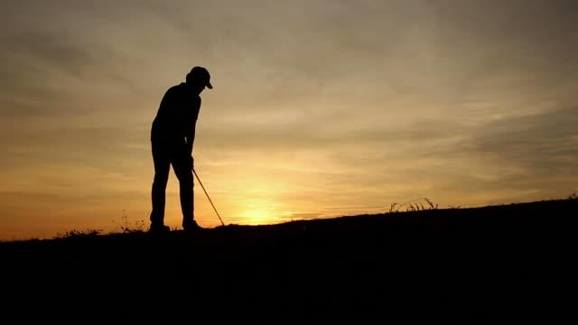 vidéos et rushes de silhouette golfeur au coucher du soleil - swing de golf