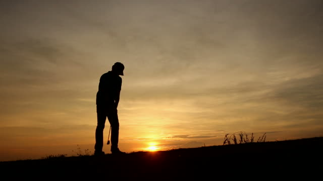 silhouette golfer at sunset - golfer stock videos and b-roll footage