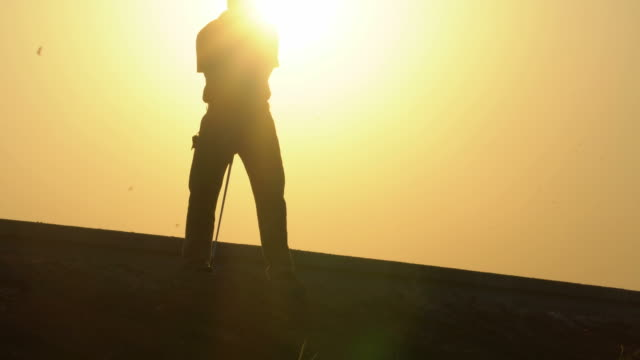 vídeos de stock e filmes b-roll de silhouette golfer at sunset - golfe