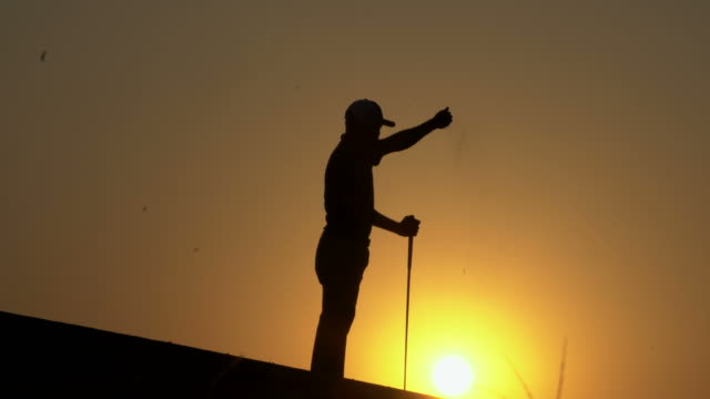 silhouette golfer at sunset - golf swing silhouette stock videos & royalty-free footage