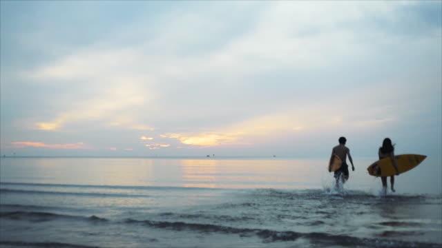 silhuett grupp av asien vän håller surfbräda som körs på stranden sommarsemester. slow motion scen grupp turister hade roligt och avkopplande när du besöker havet under soluppgång och solnedgång. - surfbräda bildbanksvideor och videomaterial från bakom kulisserna