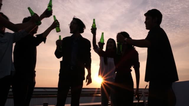 silhouette group of friends enjoying party and throwing confetti. friends having fun at rooftop party.group of friends at club having fun. new year's party - building terrace stock videos & royalty-free footage