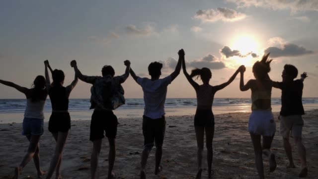 silhouette group of friends having fun on the beach.happy smiling friends running seaside sea ocean holiday travel.vacations - istock - successo video stock e b–roll