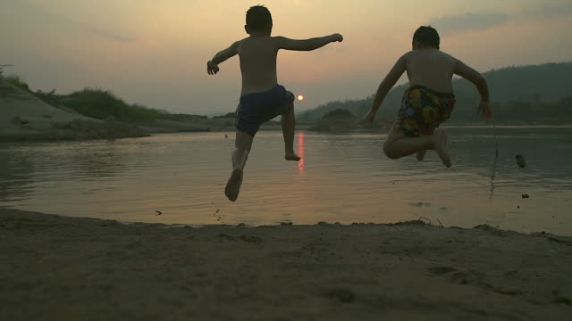 Silhouette happy child splashing played in pond at sunset.(Slow motion)