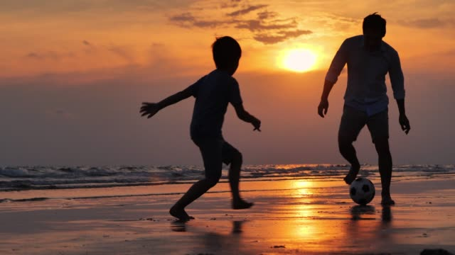 vídeos de stock e filmes b-roll de silhouette happy father and son having fun playing football on the beach at sunset.happy family enjoy summer vacation on the beach.holiday travel concept.vacations - istock - futebol