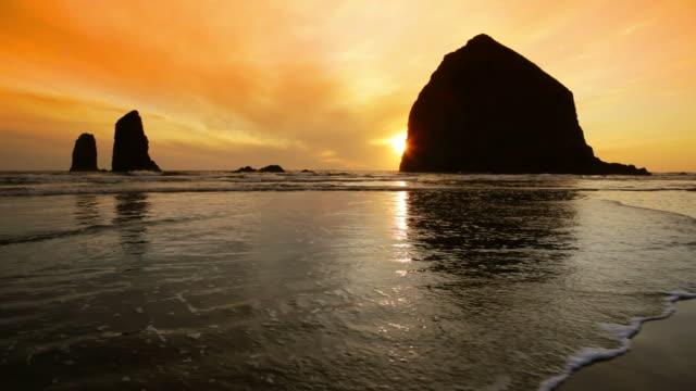 ls, silhouette haystack rock, sunset, cannon beach, oregon - haystack rock stock videos & royalty-free footage