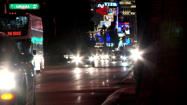 WS Silhouette headlights of various vehicles in traffic driving toward frame partial lights of hotels casinos in distant down street BG NV