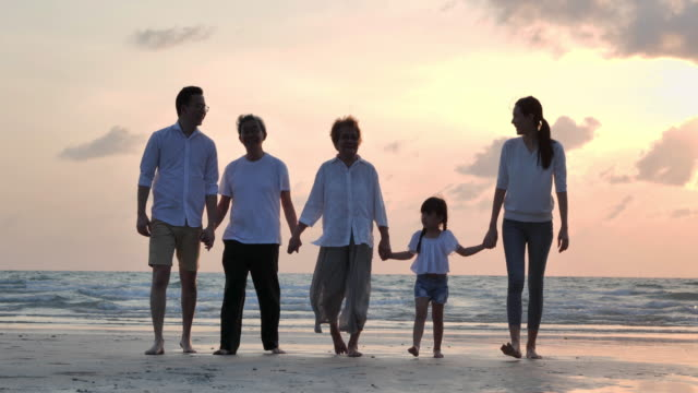 silhouette joyful asian large family walking to sunset sea surf on sand beach during covid-19 lockdown.social distancing,family,lifestyle,social distancing. - enjoyment stock videos & royalty-free footage