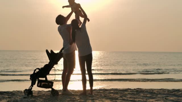 silhouette joyful father,mother,baby son having fun along edge of sunset sea surf on sand beach.active parents and people outdoor activity on summer vacations with baby.happy family holidays.family,lifestyle,people,life insurance,vacations - istock - east asian ethnicity video stock e b–roll
