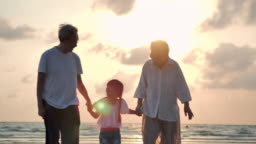 Silhouette joyful grandfather,grandmother and granddaughter holding hand and walking to sunset sea surf on sand beach. Family, Lifestyle, People, Children,Life insurance, Elderly, Vacations, Relationship, Holiday, Retirement, Healthy care concept.