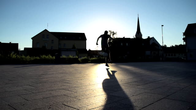 hd super slow-mo: silhouette juggling a ball - soccer player stock videos and b-roll footage