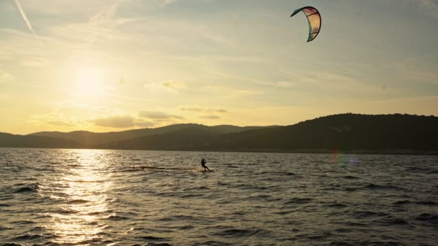 4k silhouette kite sailing on tranquil sunset ocean, real time - kite sailing stock videos and b-roll footage