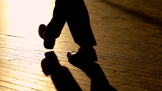 silhouette legs of businessman walking in slow motion - controluce video stock e b–roll