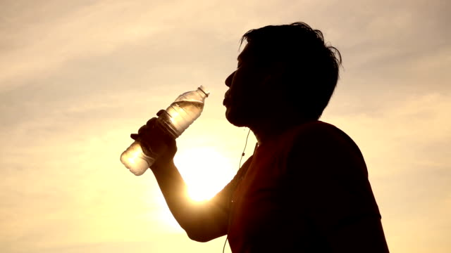 SLO MO Silhouette man drinking water after running exercising training