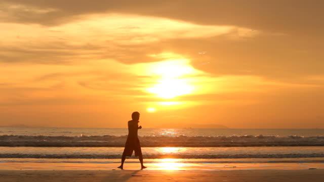 vídeos y material grabado en eventos de stock de silueta hombre ejercicio y relájese en la playa - turismo vacaciones