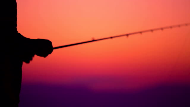 Silhouette man fishing