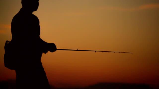 vidéos et rushes de silhouette homme pêche - un seul homme d'âge moyen