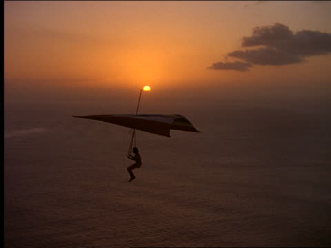 Silhouette man hang gliding over ocean at sunset