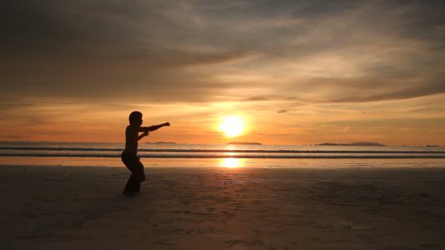 vidéos et rushes de silhouette homme pratique de tai chi sur la plage - karaté