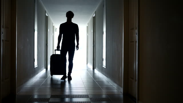 silhouette man walking with luggage out the room - inn stock videos and b-roll footage