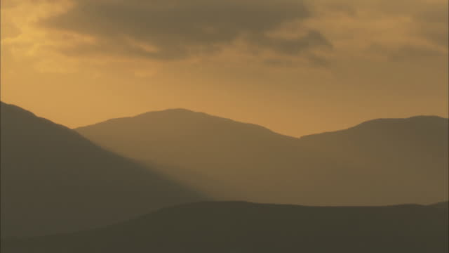 ws silhouette misty hills against sunrise in the hebrides on the west coast of scotland - hebrides stock videos & royalty-free footage