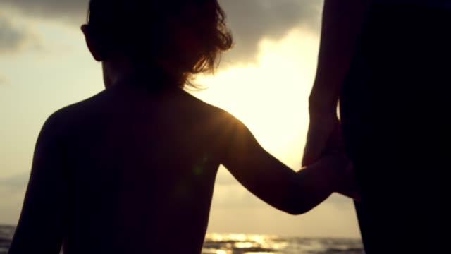 silhouette : mom and her son relaxing on the beach. - holding hands stock videos & royalty-free footage
