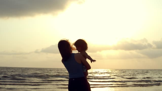 silhouette : mom and her son relaxing on the beach. - figlio maschio video stock e b–roll